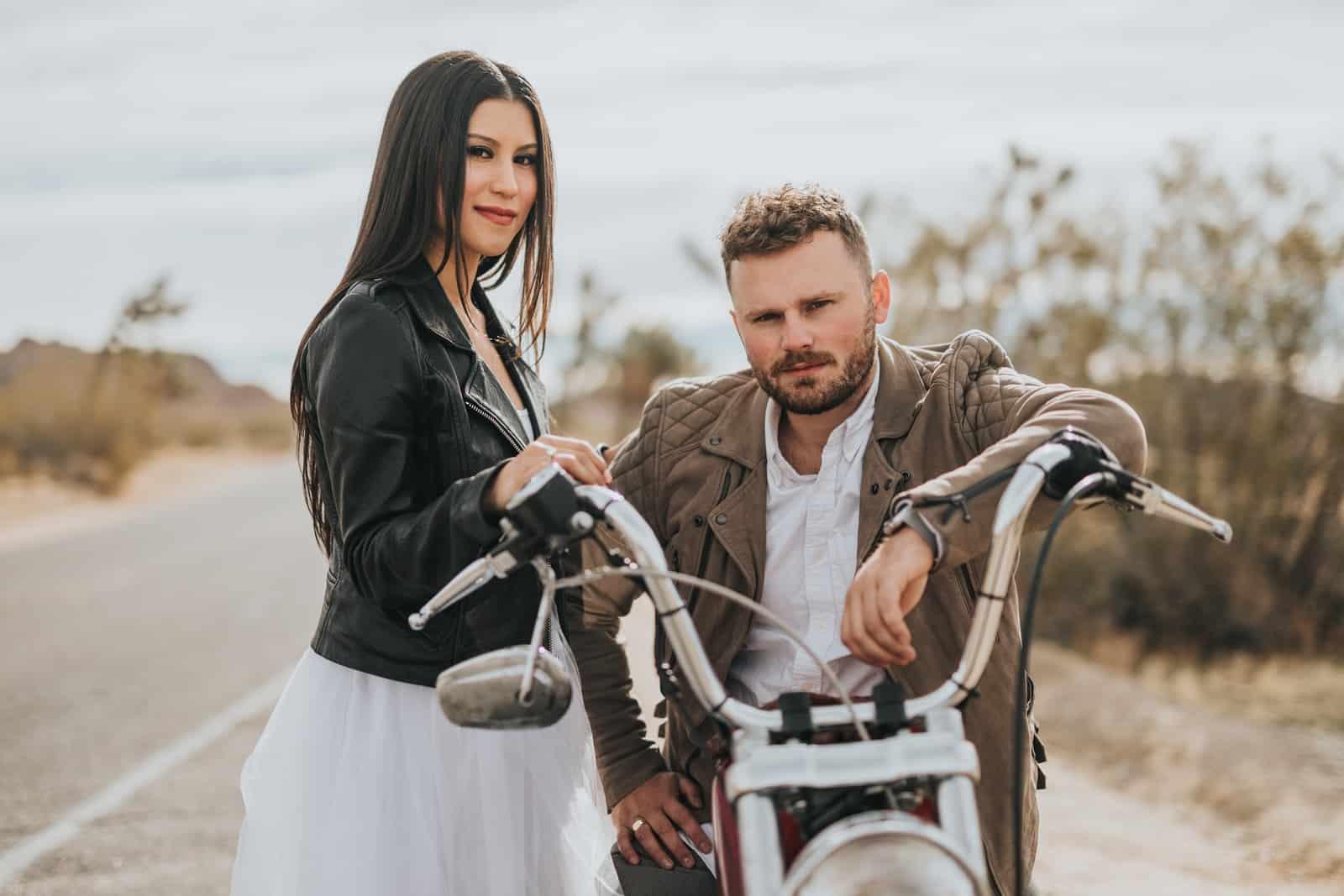man sitting on motorcycle beside woman